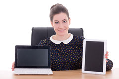 Beautiful business woman sitting in office and showing laptop an. D tablet pc with empty screen isolated on white background royalty free stock image