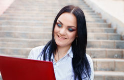 Beautiful business woman sitting on stairs with laptop Royalty Free Stock Photos