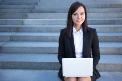 Beautiful business woman sitting on stairs with laptop Royalty Free Stock Photography