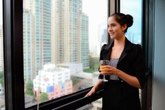 Smile of beautiful business woman at the window with champagne royalty free stock photography