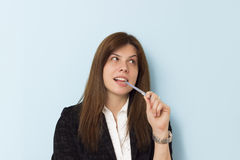 Beautiful business woman smiling and thinking, biting on a pen. Stock Photography