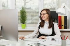 Beautiful business woman in suit and glasses working at computer with documents in light office royalty free stock photo