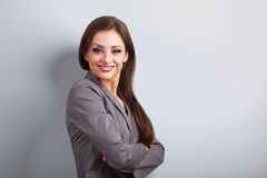 Beautiful business woman in suit smiling on blue background with Royalty Free Stock Images