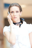 Beautiful business woman talking on cell phone. Over business background Stock Image