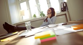 Beautiful business woman talking on cell phone. Smiling and beautiful young businesswoman sitting at her desk with legs on table talking on mobile phone smiling Stock Photo