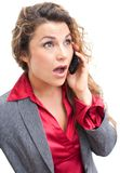 Beautiful business woman talking on cellphone in shock Stock Images