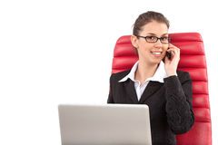 Beautiful business woman talking on mobile phone sitting on a red chair in office Royalty Free Stock Photography