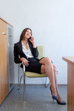 Beautiful business woman talking on the mobile phone and smiling, on chair in office Stock Photography