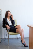 Beautiful business woman talking on the mobile phone and smiling, on chair in office Stock Photos