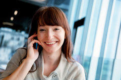 Beautiful business woman talking on mobile phone and smiling. Looking at camera Royalty Free Stock Photo