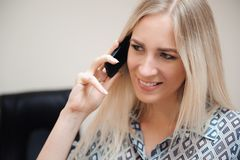 Beautiful business woman talking on mobile phone. Young female model work with sales in bright office. royalty free stock photography