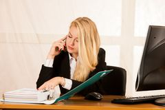Beautiful business woman talks on a smart phone in her office at. Desk stock image