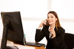 Beautiful business woman talks on smert phone in office at her d. Esk Stock Image