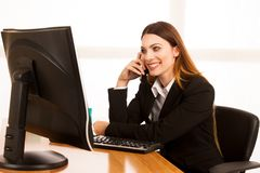 Beautiful business woman talks on smert phone in office at her d. Esk Stock Photography