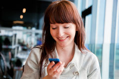 Beautiful business woman talking on mobile phone and smiling. Beautiful business woman texting on mobile phone and smiling, sitting in the corporate restaurant Stock Photography