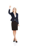 Beautiful business woman is touching an abstract space above her Royalty Free Stock Image