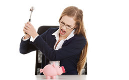 Beautiful business woman is trying to destroy piggy bank with ha Stock Image