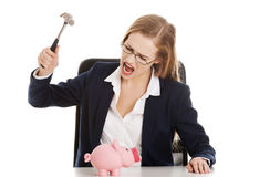 Beautiful business woman is trying to destroy piggy bank with ha Royalty Free Stock Photos