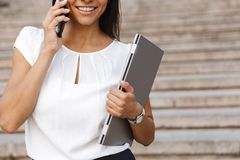 Beautiful business woman walking outdoors talking by mobile phone. Cropped image of a beautiful business woman walking outdoors talking by mobile phone royalty free stock image