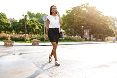 Beautiful business woman walking outdoors talking by mobile phone. Image of a beautiful business woman walking outdoors talking by mobile phone royalty free stock images