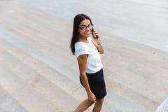 Beautiful business woman walking outdoors talking by mobile phone. Image of a beautiful business woman walking outdoors talking by mobile phone stock photos