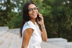 Beautiful business woman walking outdoors talking by mobile phone stock photos