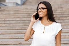 Beautiful business woman walking outdoors talking by mobile phone. Image of a beautiful business woman walking outdoors talking by mobile phone royalty free stock photos
