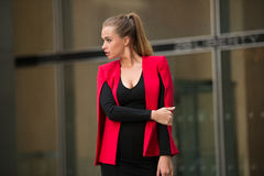 Beautiful business woman walking outside of the office and looking to the side. Sexy businesswoman wearing red jacket Royalty Free Stock Photos