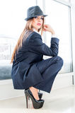 Beautiful business woman wearing man's suit, hat and high heels in office. Young business fashion woman looking bossy wearing man's suit, stylish hat and high Stock Photography