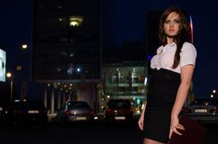 Beautiful business woman in a white shirt. And black skirt holding a briefcase at night, office buildings in the background Stock Images