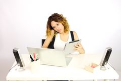 Beautiful business woman working at desk with tablet and pc talking on the phone Stock Photography