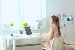 Beautiful business woman working at her desk with headset and laptop Royalty Free Stock Image