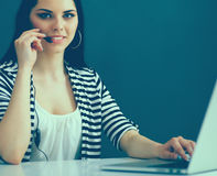 Beautiful business woman working at her desk with headset and laptop Royalty Free Stock Photo