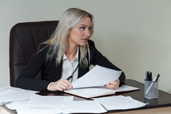 Beautiful business woman working at her office desk with documents. Beautiful business woman working at her office desk with documents Stock Images