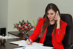 Beautiful business woman working at her office desk with documents and talking on the phone. Beautiful business woman working at her office desk with documents Stock Images