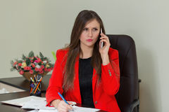 Beautiful business woman working at her office desk with documents and talking on the phone. Beautiful business woman working at her office desk with documents Stock Photography