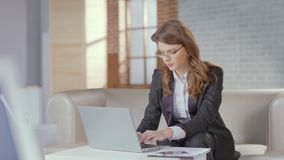 Beautiful business woman working on laptop in expensive office. Stock footage stock video footage