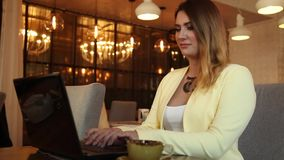 Beautiful business woman working using a mobile computer in a cafe. Beautiful business woman with long hair running using a mobile computer in dark color in a stock footage