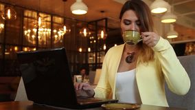 Beautiful business woman working using a mobile computer and drinking tea. Beautiful business woman with long hair running using a mobile computer of dark color stock video footage
