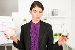 Beautiful business  woman worry about heating bills. Holding a piggy bank Royalty Free Stock Photography