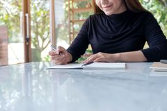 A beautiful business woman writing on blank notebook on table with green nature background. Closeup image of a beautiful business woman writing on blank notebook royalty free stock photography
