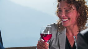 Beautiful business women taking a sip. Close-up slow motion footage of a business partners toasting on a good deal in the middle of the beautiful landscape on stock footage