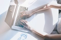 Beautiful business women typing hand on a laptop computer while sitting at the wooden table in light coloured living. Room of modern house.Top view.Sunny day Royalty Free Stock Image