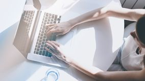 Beautiful business women typing hand on a laptop computer while sitting at the wooden table in light coloured living. Room of modern house.Sunlight effect Royalty Free Stock Image