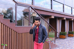 Beautiful Businesslike Muslim Man Goes And Speaks by Phone and S. Confident Attractive Young Guy Muslim Businessman Goes Slowly Along Wall, Holding Phone in Hand Stock Photo
