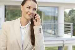 Beautiful businesswoman answering cell phone against office building Royalty Free Stock Photo