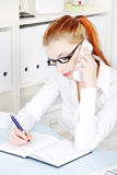 Beautiful businesswoman answering the phone. Stock Images