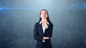 Beautiful businesswoman with arms folded looking up at copyspace. Standing over gray background. Stock Photo