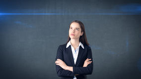Beautiful businesswoman with arms folded looking up at copyspace. Standing over gray background. Royalty Free Stock Photography
