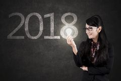 Beautiful businesswoman with bulb and numbers 2018. Beautiful businesswoman holding a light bulb while standing with numbers 2018 on the blackboard Stock Photography